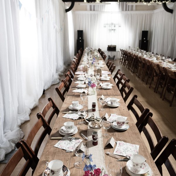 Rustic tables and wooden folding chairs at a wedding - BE Event Hire