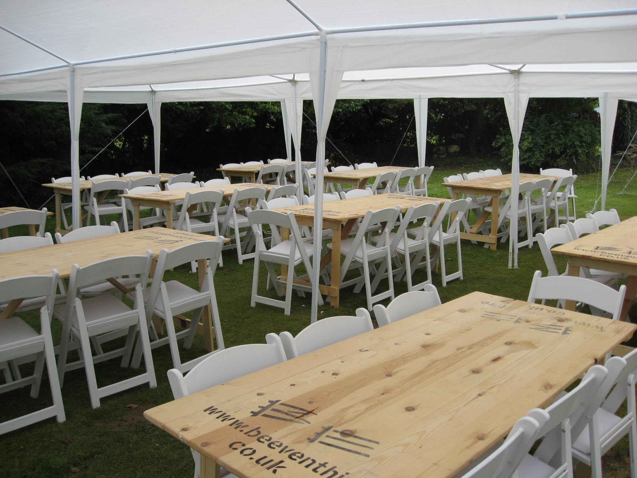 White folding chair and wooden trestle tables hired for outdoor wedding - BE Event Hire